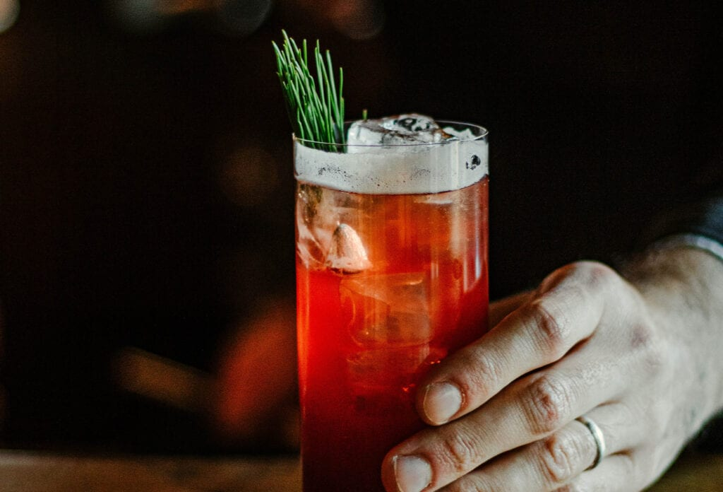 Man holding red cocktail